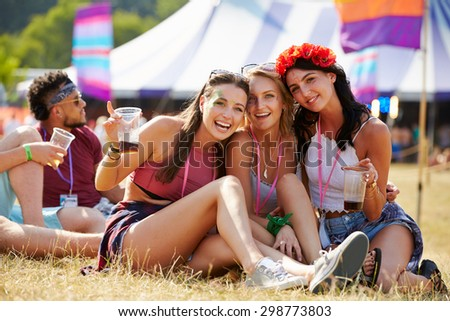 Friends sitting on the grass having fun at a music festival - stock photo