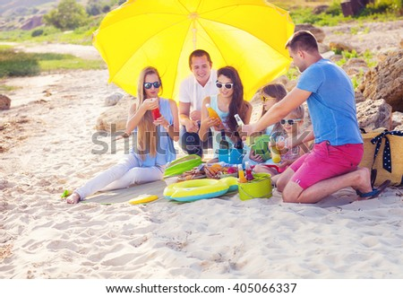 Friends sitting on the sand at the beach at the summer picnic. Green bucket with lemonade - stock photo