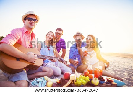 Friends sitting on the sand at the beach in circle. One man is playing guitar - stock photo