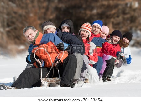 Friends sliding and having fun in winter - stock photo