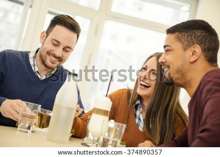 Friends smiling and sitting in a cafe,drinking coffee and enjoying together - stock photo