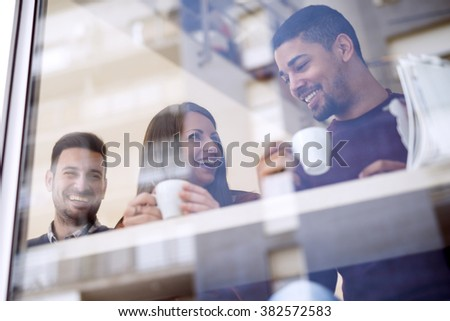 Friends smiling and sitting in a coffee shop,talking and drinking coffee - stock photo