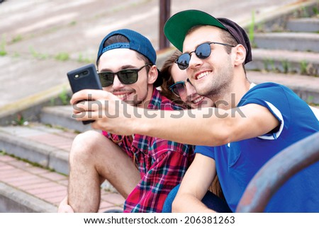 Friends smiling at the camera. Young friends have fun together on the street and smile at each other. Funny guys make Selfie - stock photo