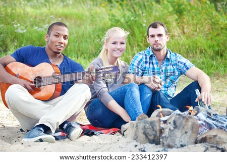 Friends spending time outside at campfire. - stock photo