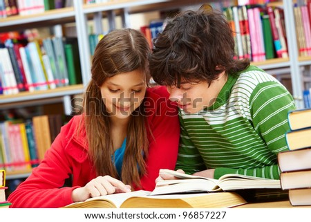 Friends spending time together studying at library - stock photo