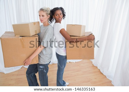 Friends standing back to back holding moving boxes in their new home - stock photo