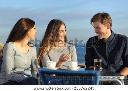 Friends talking in a restaurant terrace on the beach in a sunny day - stock photo