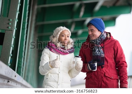 Friends talking while walking outdoors - stock photo