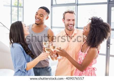 Friends toasting wine glasses at home - stock photo