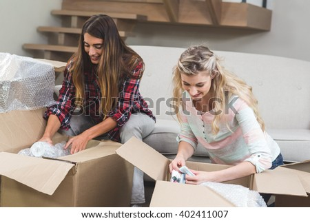 Friends unpacking carton boxes in their new house - stock photo