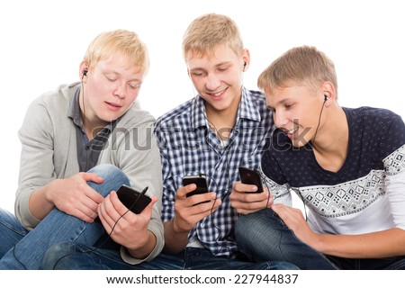 Friends use smartphones sitting on the carpet. Two of the boys twin brothers. - stock photo