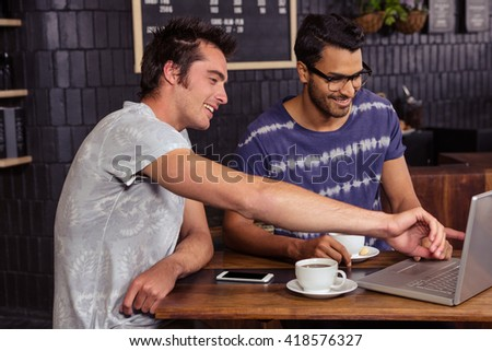 Friends using a laptop in a coffee shop - stock photo
