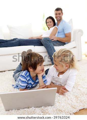 Friends using a laptop on floor and couple lying on sofa - stock photo