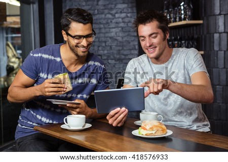 Friends using a tablet while eating sandwiches in a coffee shop - stock photo