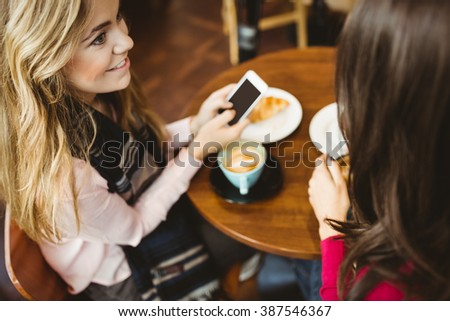 Friends using their smartphone in cafe - stock photo