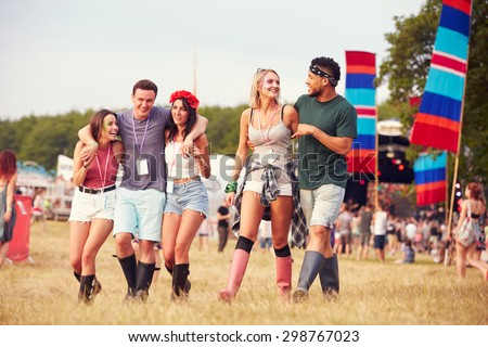 Friends walking through a music festival site - stock photo