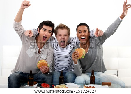 Friends watching a football game together - stock photo