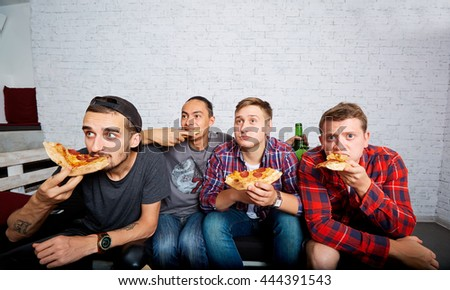 Friends watching TV with surprise, eating pizza close-up. Fans were frozen in anticipation. Friends sitting on the couch watching TV. - stock photo