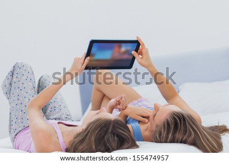 Friends wearing pajamas holding tablet in bed - stock photo