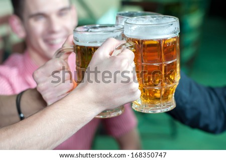 Friends with a fresh beer in a Beer pub. close-up on beer stein - stock photo