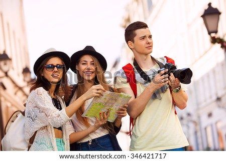 Friends with camera and city map as tourists - stock photo