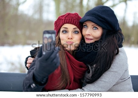 Friends with camera phone having fun by making faces - stock photo