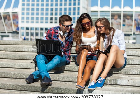 friends with laptop sitting on a steps outdoors - stock photo