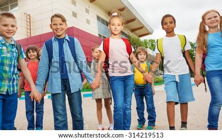 Friends with rucksacks walk near school building - stock photo