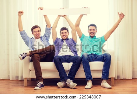friendship and advertising concept - smiling male friends holding white blank banner - stock photo