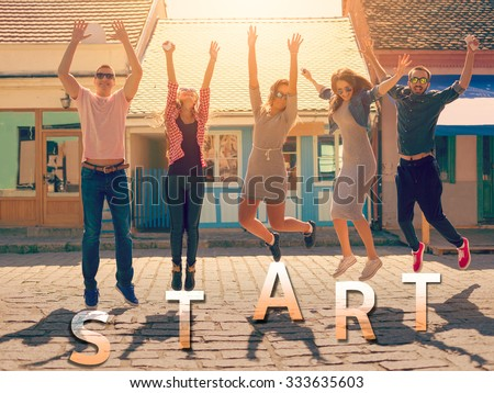 Friendship and new begining concept. Group of teenagers having good fun on the city streets jumping up in air with text start beneath their feet. - stock photo