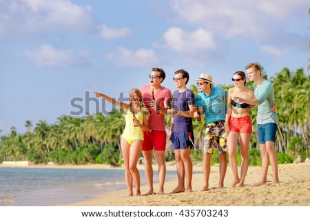 Friendship and vacation. Beach party. Group of amazed friends with bottles of beer looking  and pointing away. - stock photo