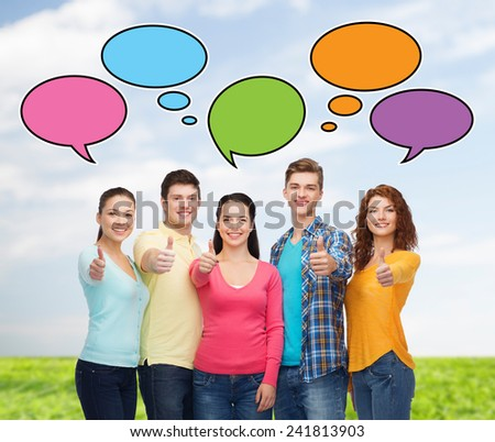 friendship, communication, gesture and people concept - group of smiling teenagers showing thumbs up over sky and grass with text bubbles - stock photo