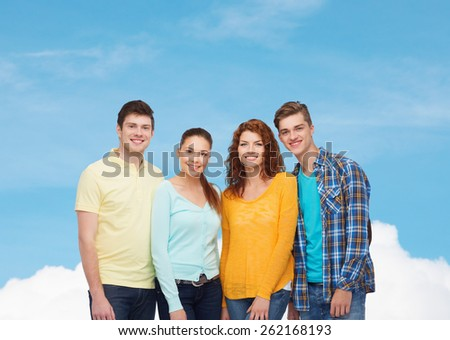 friendship, dream and people concept - group of smiling teenagers standing over blue sky with white cloud background - stock photo