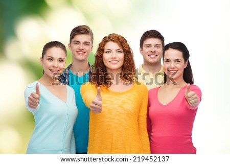 friendship, ecology, gesture and people concept - group of smiling teenagers showing thumbs up over green background - stock photo