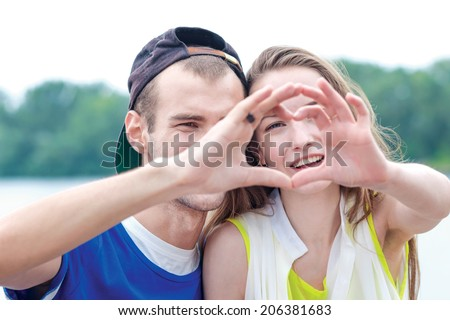 Friendship forever. Best friends have fun on the street near the river. Two guys show of hands heart - stock photo