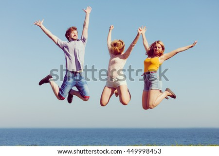 Friendship freedom summer holidays concept. Group of friends boy two girls jumping outdoor against sky - stock photo