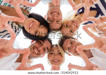 friendship, happiness and people concept - smiling friends in circle showing victory sign - stock photo