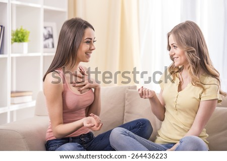 friendship, happiness and people concept -Young beauty girls talking at home. - stock photo