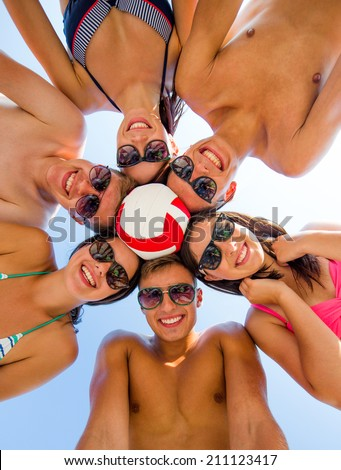 friendship, happiness, summer vacation, holidays and people concept - group of smiling friends wearing swimwear standing in circle with volleyball over blue sky - stock photo