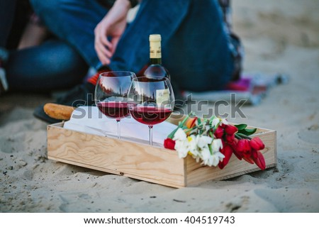 Friendship, happiness, summer vacation, holidays and people concept - Two glasses with wine, flowers and bread in wooden box, on beach and couple sitting on background out of focus. - stock photo