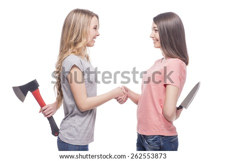 Friendship is over. Two smiling women standing face to face and holding knife and  axe.  isolated on white background. - stock photo