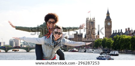 friendship, leisure, international, freedom and people concept - happy teenage couple in shades having fun over houses of parliament and thames river in london background - stock photo