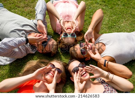 friendship, leisure, summer and people concept - group of smiling friends lying on grass in circle outdoors - stock photo