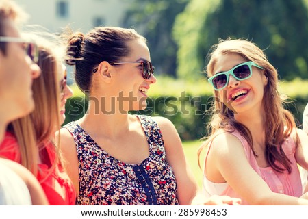 friendship, leisure, summer and people concept - group of smiling friends outdoors sitting on grass in park - stock photo