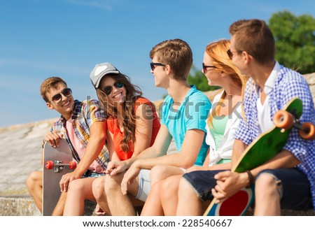 friendship, leisure, summer and people concept - group of smiling friends with skateboards sitting on city street - stock photo