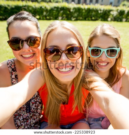 friendship, leisure, summer, technology and people concept - group of smiling teen girls taking selfie with smartphone camera or tablet pc in park - stock photo