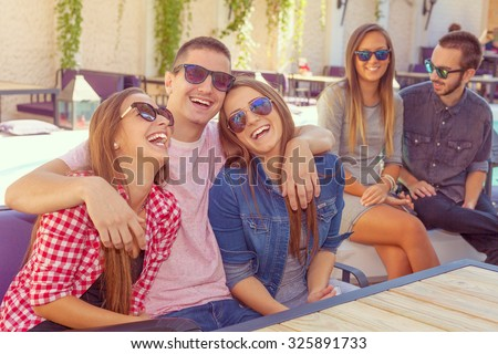 Friendship - lifestyle concept. Group of young and cheerful friends having fun near pool in the cafe.Young boy put arms around each other of his female friends. - stock photo