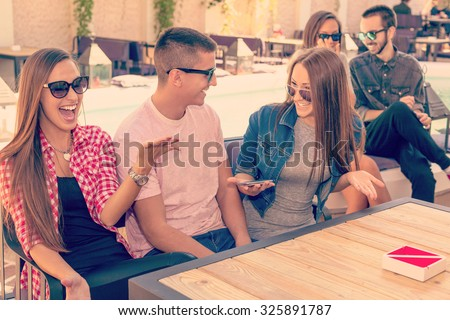 Friendship - lifestyle concept. Group of young and cheerful friends having fun near pool in the cafe. - stock photo