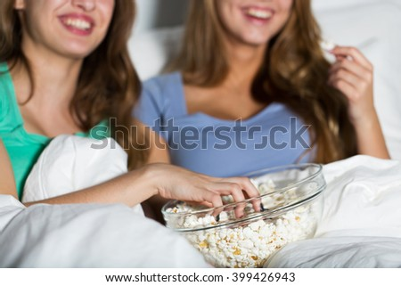 friendship, people, pajama party, entertainment and junk food concept - close up of happy friends or teenage girls eating popcorn and watching movie or tv series at home - stock photo