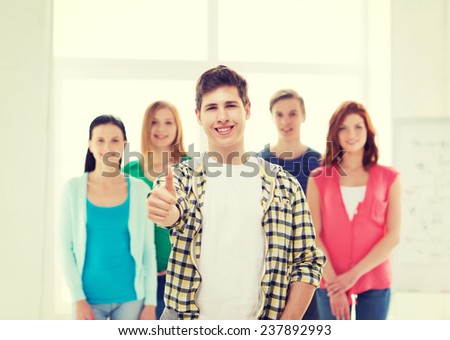 friendship, school and education concept - male student with classmates showing thumbs up gesture - stock photo